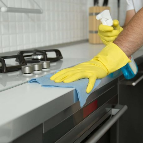Close up of male hands in rubber yellow gloves cleaning the cooker panel at home kitchen. Home, housekeeping concept
