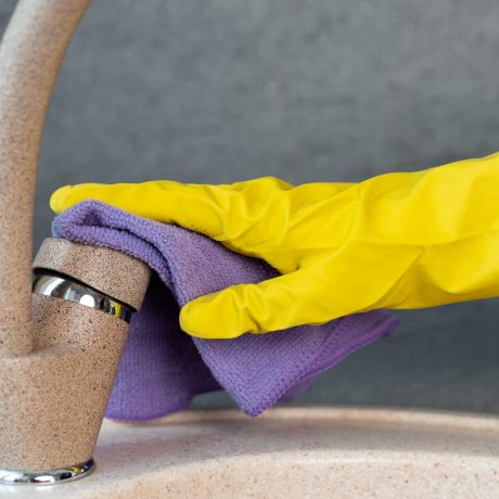 Hands in yellow gloves cleaning a sink with a sponge close up