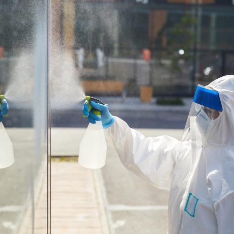 Side view portrait of female worker wearing protective suit spraying chemicals over building wall during disinfection, copy space